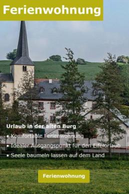 Ein Dorf in der Eifel. Rechts der Kirchtum. Links die alte Burg von Hersdorf. Die Burg ist zu Ferienwohnungen umgebaut.