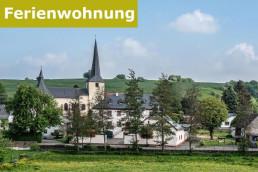 Blick auf ein Dorf in der Eifel. im Mittelpunkt der grünen Landschaft liegt die Kirche, daneben die alte Burg mit der Ferienwohnung